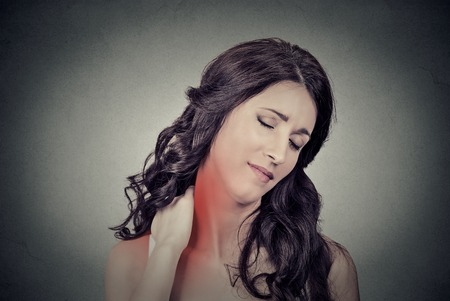 nape: Back and spine disease. Closeup portrait tired woman massaging her painful neck colored in red isolated on gray wall background. Human face expression. Chronic fatigue disease