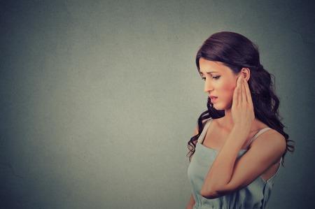 dolor de oido: Tinnitus. Perfil lateral mujer joven enferma que tiene dolor de o�do tocar su templo principal dolorosa aislado en el fondo gris de la pared con el espacio de la copia en blanco