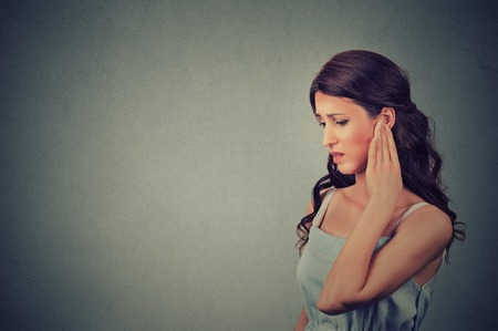 plug: Tinnitus. Side profile sick young woman having ear pain touching her painful head temple isolated on gray wall background with blank copy space