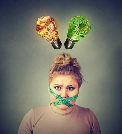 Concepto de la dieta estrés restricción. Mujer frustrada joven con una cinta métrica alrededor de su boca la comida chatarra y los vegetales verdes como forma de bombilla encima de la cabeza. Expresión facial. Elección nutrición adecuada Foto de archivo