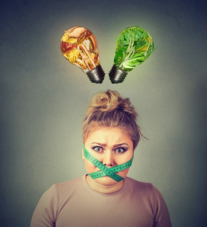 cravings: Diet restriction stress concept. Young frustrated woman with a measuring tape around her mouth junk food and green vegetables shaped as light bulb above head. Face expression. Right nutrition choice Stock Photo