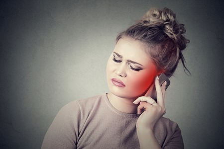 handphone: girl on the phone with headache. Upset unhappy female talking on phone isolated grey wall background. Negative human emotion face expression feeling life reaction. Cellular mobile radiation concept