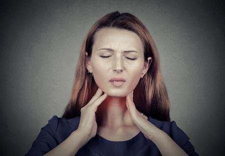 목이 근접 촬영 여자는 그녀의 목은 붉은 색 취소를 터치. 아픈 젊은 여자는 그녀의 목에 통증이 회색 벽 배경에 고립 된 데 스톡 콘텐츠
