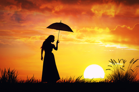 woman umbrella: A silhouette of a slim young woman in dress with umbrella enjoying sunset
