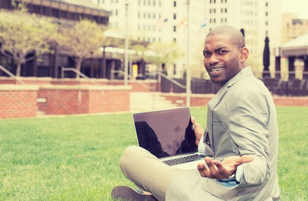 pissed off: Frustrated angry business man with laptop sitting outdoors corporate office city urban background Stock Photo