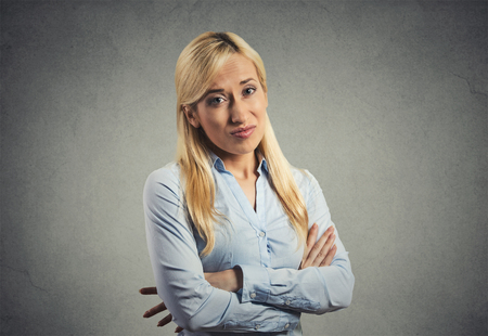 bitchy: grumpy skeptical blonde woman isolated on gray background