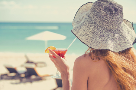 caribbeans: Back view young woman wearing a bikini holding a cocktail enjoying ocean view. Summer vacation travel concept Stock Photo
