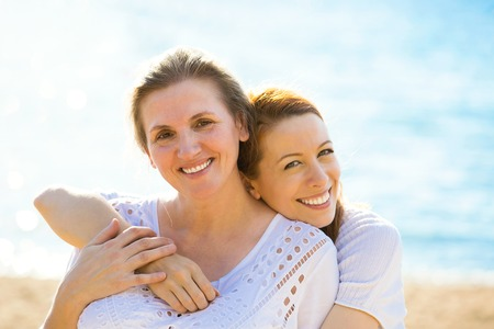 life style: Portrait two women mother and adult daughter enjoying vacation on the beach