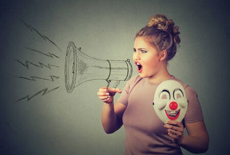 woman with clown mask screaming in megaphone Stock Photo