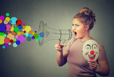 trickster: Portrait young woman with clown mask screaming in megaphone isolated on gray background. Negative face expression emotion feeling. Propaganda, breaking news, power, social media communication concept