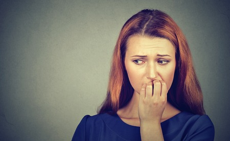 insecure: Closeup portrait young nervous woman biting her fingernails craving something or anxious, isolated on gray wall background. Negative human emotions facial expression feeling