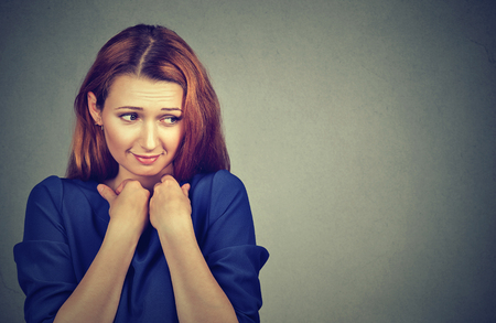 lack of confidence: Lack of confidence. Shy young woman feels awkward isolated on grey wall background. Human emotion body language life perception Stock Photo