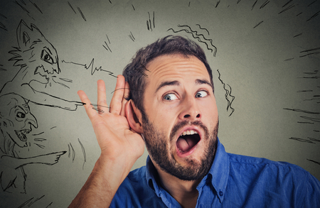 inner: Closeup young man with hand to ear gesture and evil voices screaming blaming him isolated on gray wall background. Human emotion face expression