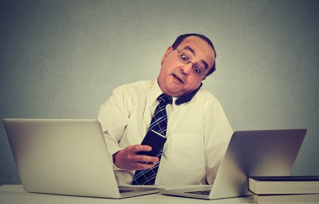 errands: Multitasking middle aged business man working at his office desk isolated on gray wall background. Busy life of company manager corporate executive. Many errands concept Stock Photo