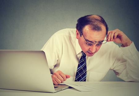 revisando documentos: Confundido hombre de negocios sorprendido mirando a los documentos. Sacudida eléctrica media corporativo ejecutivo edad que trabaja en su escritorio en la oficina papeleo revisión