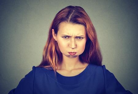 Retrato de mujer joven enojado, hinchando las mejillas a punto de tener depresión nerviosa, aislados sobre fondo gris. emociones humanas negativas expresión facial actitud sentimientos