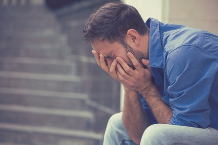 agotado: perfil lateral subrayó hombre joven llorando triste sentado fuera sosteniendo la cabeza con las manos mirando hacia abajo. sentimientos emociones humanas Foto de archivo