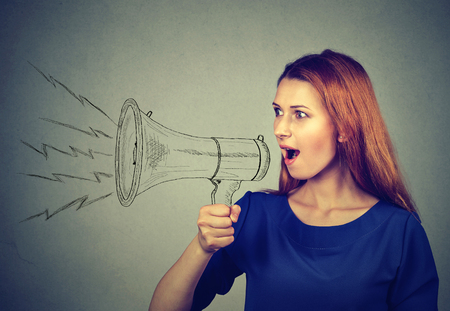spread: Portrait angry young woman screaming in megaphone isolated on grey wall background. Negative face expression emotion feelings. Propaganda, breaking news, power, social media communication concept Stock Photo