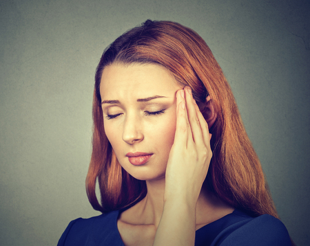 neuralgia: woman having headache, migraine isolated on gray wall background