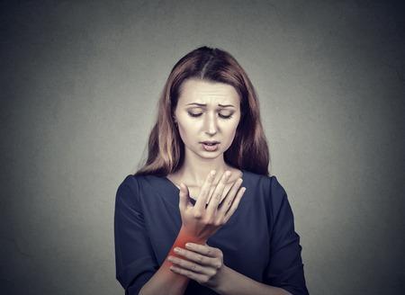 회색 벽 배경에 고립 된 그녀의 고통스러운 손목을 잡고하는 젊은 여자. 붉은 색 점으로 표시된 통증 부위가 골절됩니다. 부정적인 얼굴 표현