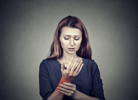 sprain: Young woman holding her painful wrist isolated on gray wall background. Sprain pain location indicated by red spot. Negative face expression