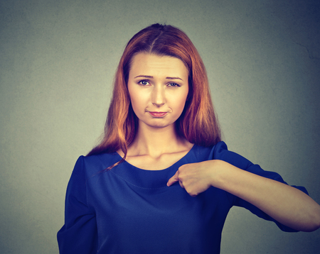 libel: Closeup portrait of angry, unhappy, annoyed young woman, getting mad, asking question you talking to me, you mean me? Isolated gray background. Negative human emotions, facial expressions