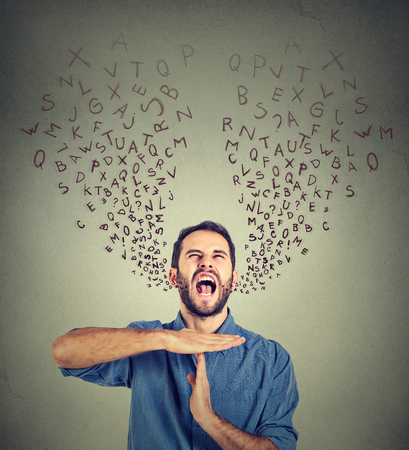foreign bodies: Young man showing time out hand gesture, frustrated screaming to stop alphabet letters coming out of mouth isolated on gray background. Too many things to do. Human emotions face expression reaction