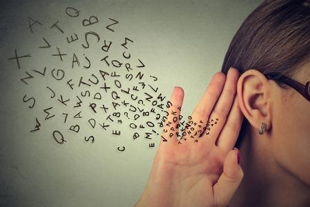 De vrouw houdt haar hand in de buurt van oor en luistert aandachtig alfabet letters vliegen in geïsoleerde op grijze muur achtergrond Stockfoto