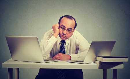 Bored business man sitting in front of two laptop computers