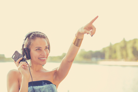 Happy woman listening to music outdoors photo