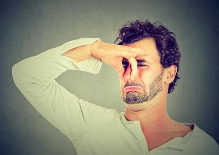 olfato: hombre joven con disgusto en su rostro pellizca la nariz, algo huele mal, muy mal olor aislados sobre fondo gris. La emoción negativa la expresión facial Foto de archivo
