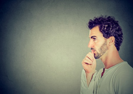 side profile: Worried man sucking his thumb isolated on gray wall background