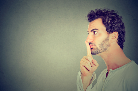 silence quiet gesture. Side profile serious young man making hush sign isolated on gray wall background