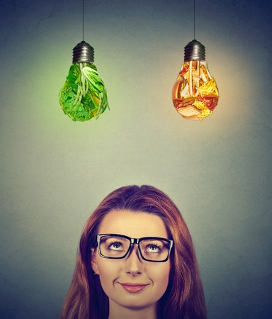 vision loss: Woman in glasses thinking looking up at junk food and green vegetables light bulbs isolated on gray wall background. Diet choice right nutrition healthy lifestyle concept Stock Photo