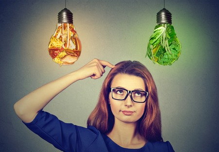 cravings: Woman in glasses thinking looking up at junk food and green vegetables light bulbs isolated on gray wall background. Diet choice right nutrition healthy lifestyle concept Stock Photo