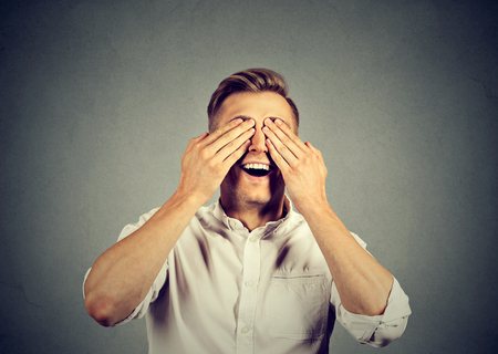 handsome young man: Surprised man covering his eyes with hands Stock Photo