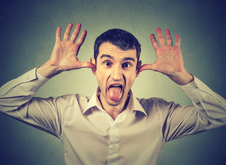 provoke: Young angry man, sticking out tongue at you, camera gesture, thumbs hands on temple, isolated on white background. Negative human emotions
