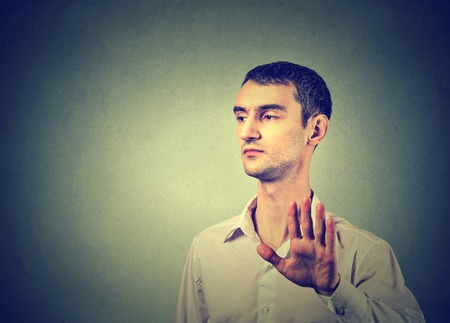 bad attitude: Young annoyed angry man with bad attitude giving talk to hand gesture with palm outward isolated grey wall background. Negative human emotion face expression feeling body language