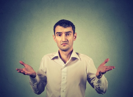 dont: Ignorance and arrogance. Young man shrugging shoulders so what I dont know gesture isolated on gray wall background. Human body language, attitude reaction Stock Photo