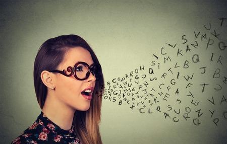 그녀의 입에서 나오는 알파벳 글자와 이야기하는 안경에 여자. 커뮤니케이션, 정보, 인텔리전스 개념