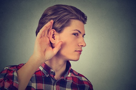 intrude: Listening man holds his hand near ear gesture