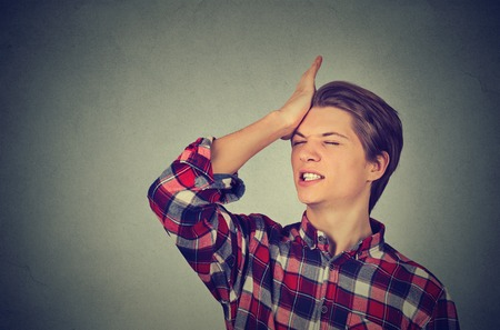 duh: Closeup portrait silly young man, slapping hand on head having a duh moment isolated on gray background. Negative human emotion facial expression feeling, body language, reaction