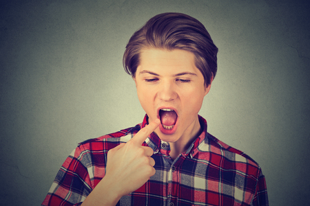 throw up: disgusted man with finger in mouth displeased about to throw up isolated on gray wall background. Human face expression, emotion, feeling, body language