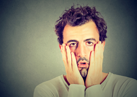 desesperado: retrato de hombre infeliz desesperada aislada sobre fondo gris de la pared