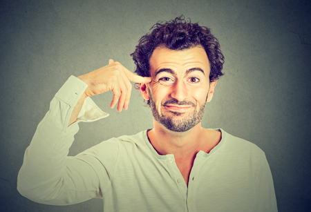 insulted: Disappointed young man gesturing with his finger against temple asking are you crazy? Isolated on gray wall background. Negative emotion facial expression feeling body language