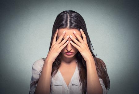 mente: Primer retrato triste mujer hermosa joven con tensionado preocupante expresión facial que cubre la cara con las manos mirando hacia abajo Foto de archivo