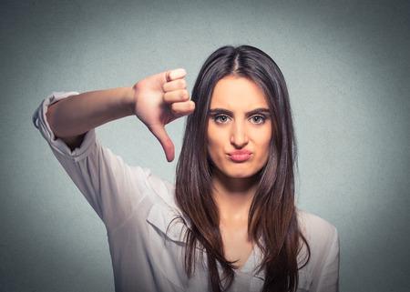 부정적인 식으로보고 회색 배경에 비 승인 제스처 아래로 엄지 손가락을주는 불행한 여자