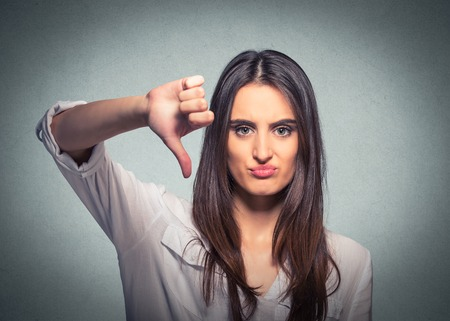 Unhappy woman giving thumb down gesture looking with negative expression and disapproval on gray background Imagens