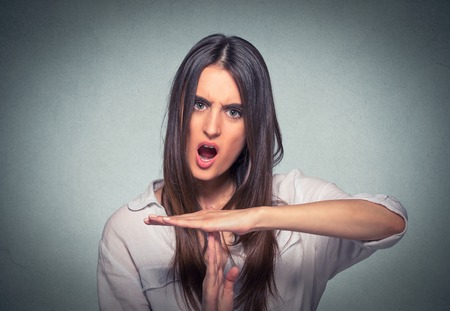 errands: Young woman showing time out hand gesture, frustrated screaming to stop isolated on gray background. Human emotions face expression reaction Stock Photo