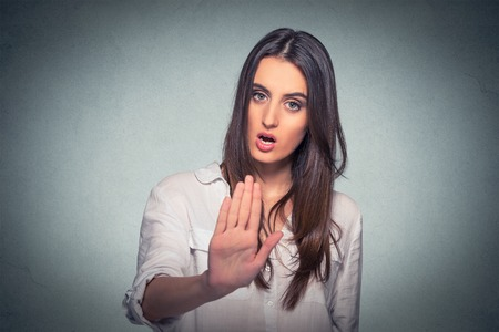 bad attitude: Young annoyed angry woman with bad attitude giving talk to hand gesture with palm outward isolated grey wall background. Negative human emotion face expression feeling body language